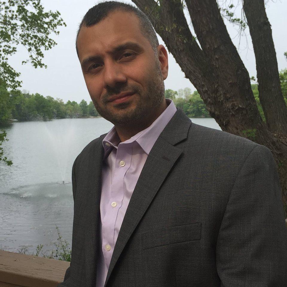 Joe Rivera standing next to a lake.